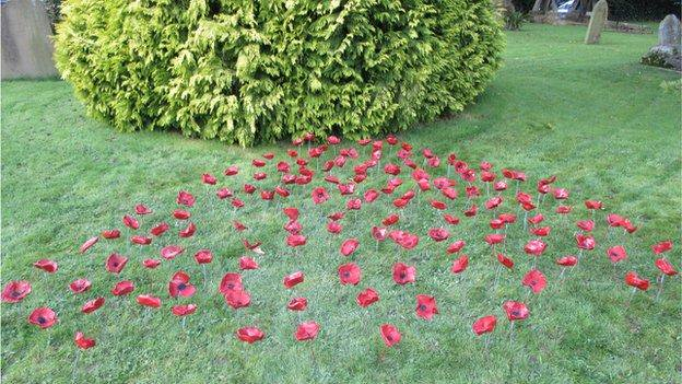 Ceramic poppies in Slinfold churchyard, made by pupils at Slinfold Primary School